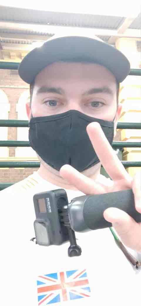 Isaac facing the camera, wearing a face mask and holding his camera