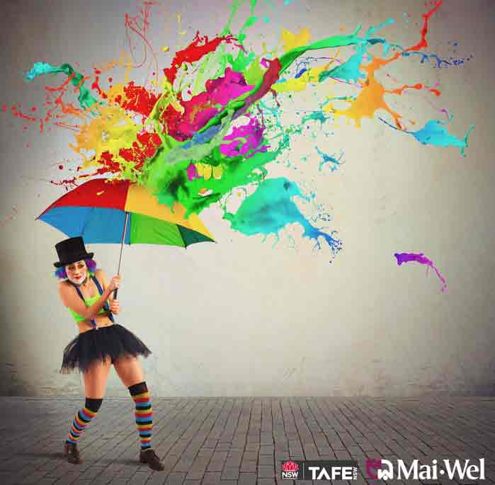A clown holding an umbrella being splashed by rainbow paint.